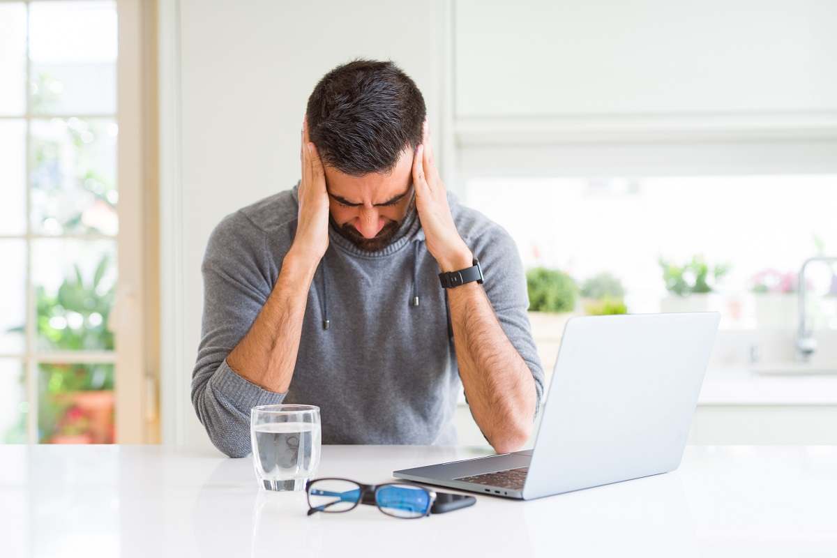 Man on laptop holding head