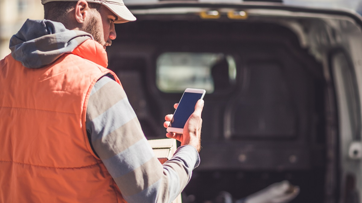 Tradesman looking at mobile phone outside