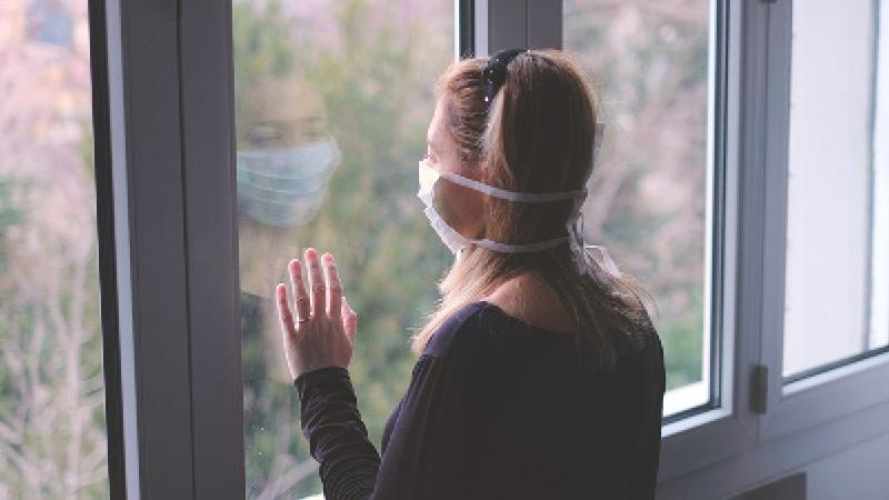 lady wearing facemask beside window